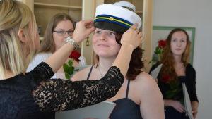Ung kvinna får sin yrkesexamensmössa.