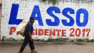 En man går förbi en väggmålning där det står: Lasso presidente 2017. Ecuador väljer ny president 2.4.2017.