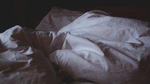 En säng med skrynkliga lakan.