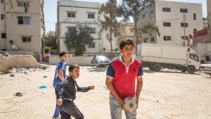 Mohammad och hans 2 kamrater spelar fotboll på en sandplan mellan husen någonstans i mellanöstern