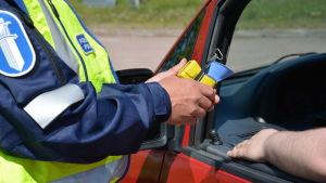 Polisen med ett blåstest i handen vid en bil.
