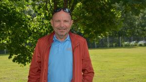 Dan Häggblom står i grönskan utomhus i blå skjorta och röd jacka och glasögon på huvudet.