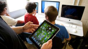 Elever jobbar vid en dator. En lärare står bredvid och håller i en pekplatta.