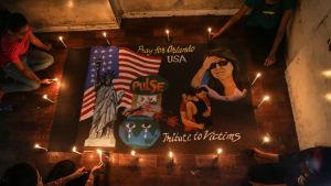 """Indiska studerande ordnar en minnesstund i Mumbai med bilder av ett gråtande jordklot, frihetsgudinnan, USA:s flagga och texterna """"Be för Orlando"""" och """"Vi hedrar offren""""."""