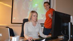 Linda Mannila spelar datorspel och David Mannström förklarar hur spelet går till.