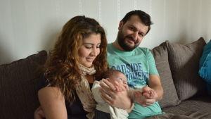 Paret Nour och Shfan sitter i soffan med sin dotter Lara i famnen.