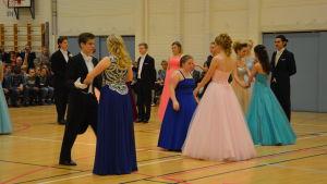 Ungdomar i långklänning och frack dansar.