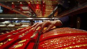 Rader med guldkedjor framställda i vitrin i guldsmedsaffär.