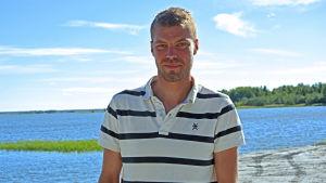 Joakim Nygård som står ute i naturen med havet i bakgrunden.