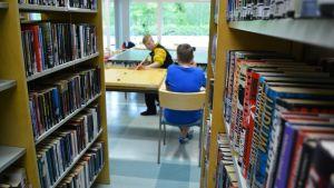 Coronaspel mellan böckerna i Strömfors gamla bibliotek.