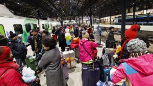 Kinesiska turister står på en perrong på Helsingfors järnvägsstation och väntar på att få stiga på tåget till Kemi, som är kraftigt försenat.