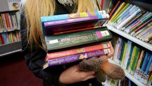En famn full med böcker.