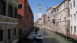 Alakerroksiltaan rapistuneita taloja kanaalin varrella Venetsiassa, taustalla hieman vino kirkontorni.