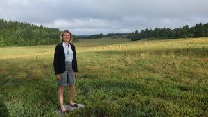 En kvinna står i en kohage med kor i bakgrunden.