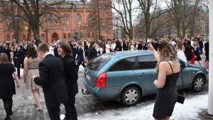 Niondeklassister i festkläder står utanför Vasa stadshus efter att byggnaden tvingades evakueras. Flera hundra personer står på gatan och i parken.