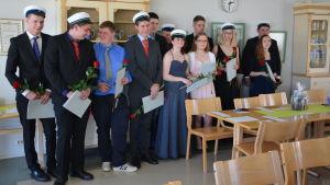 Studerande vid Axxell brusaby poserar med betyg och mössor.
