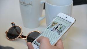 Ett par solglasögon och några kaffekoppar på ett bord. En hand håller i en smarttelefon.