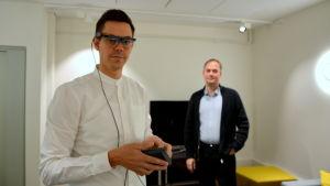 Utvecklaren Joachim Majors visar glasögonen som mäter ögonrörelser. Verksamhetschefen Kimmo Rautanen står i bakgrunden.