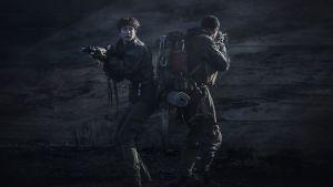 Daniels (Katherine Waterstone) och en annan man står i mörker och siktar med sina vapen.