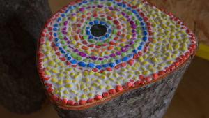 Mosaikstenar i olika färger limmade på en stubbe.