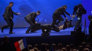 En aktivist bärs ut från scenen av Le Pens säkerhetsvakter.