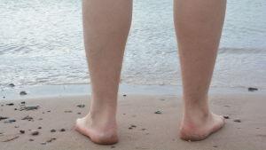 Fötter på strand.