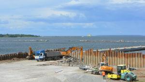 Byggarbetsplats alldeles intill havet. Vid horisonten skymtar en passagerarfärja.
