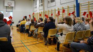 Alla närvarande på invånarmöte om skolornas framtid i östra Borgå viftar med röda lappar.