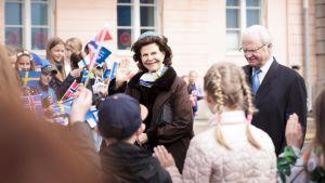 Drottning Silvia och kung Carl XVI Gustaf promenerar och vinkar till publiken på Salutorget i Helsingfors.