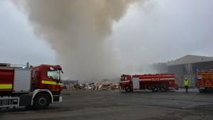 Tre brandbilar står framför en brinannde soptipp