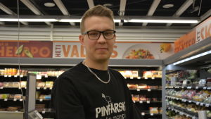 Fredrik Lönnqvist står i en livsmedelsbutik och tittar in i kameran.