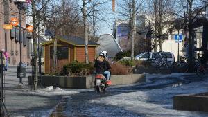 Flicka på moped kör på gågatan i Karleby