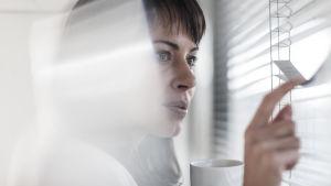 Kvinna kikar genom persienner