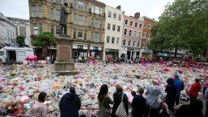 Sörjande har lagt ut blommor vid ett torg nära Machester Arena där 22 människor dödades och ett hundratal skadades för en vecka sedan
