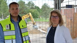Erik Rönnqvist till höger med arbetsväst på sig. Till höger står rektor Ulrica Nyström med vit kofta. I bakgrunden ser man ett byggstängsel och en grävskopa.