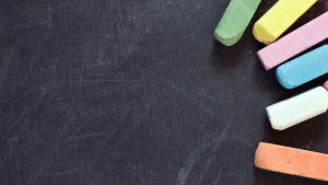 Olika färgers kritor ligger ovanpå en svart tavla.