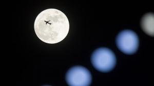 Ett jetplan flyger över månen i Hongkong.