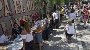 Venezuelaner i Spanien har också möjlighet att delta i söndagens inofficiella folkomröstning. Här lägger venezuelaner sina röster på Plaza de Colón i Madrid.
