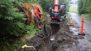 En grävmaskin gräver ett dike där det sätts ner jordkablar, luftkablarna tas alltså bort.
