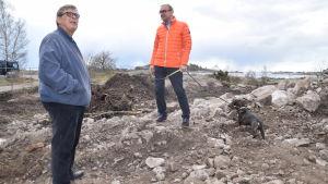 Hangös stadsdirektör Denis Strandell och Hangöbon Johannes Runeberg ser på parken på Fabriksudden där staden tar bort nedsmutsad jord och träd.