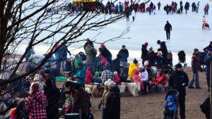 Barnfamiljer runt lägereld på sandsttranden på Sandö i Vasa