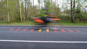 motorcykel kör över ett ingröpt trafikmärke i asfalten