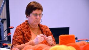 Brita Siegfrids sitter och stickar i ett klassrum. Framför henne ligger mängder av garn i olika orange nyanser.