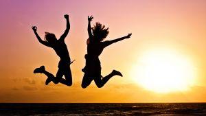 Två människor som hoppar av glädje mot solnedgången