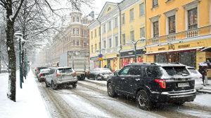 Bilar i snöfall på Norra Esplanaden i Helsingfors.