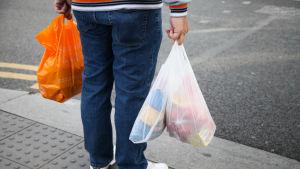 En man som håller i tre plastpåsar fyllda med matvaror.
