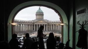 Vy från ett café i S:t Petersburg. I förgrunden syns människor som står framför ett bågformat fönster i motljus.