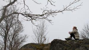 Nainen mietiskelee kevätsäässä kalliolla.