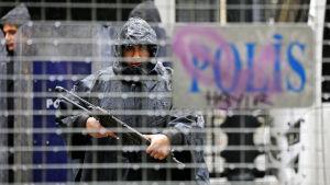 En turkisk polis patrullerar med maskinpistol i regnet i Istanbul.