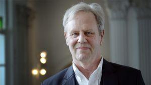 Porträtt av Göran Djupsund i vit skjorta och kavajrock.